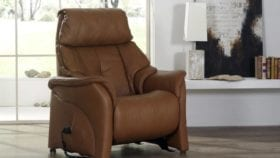 himolla Chester Riser Chair in brown leather, in living room setting.